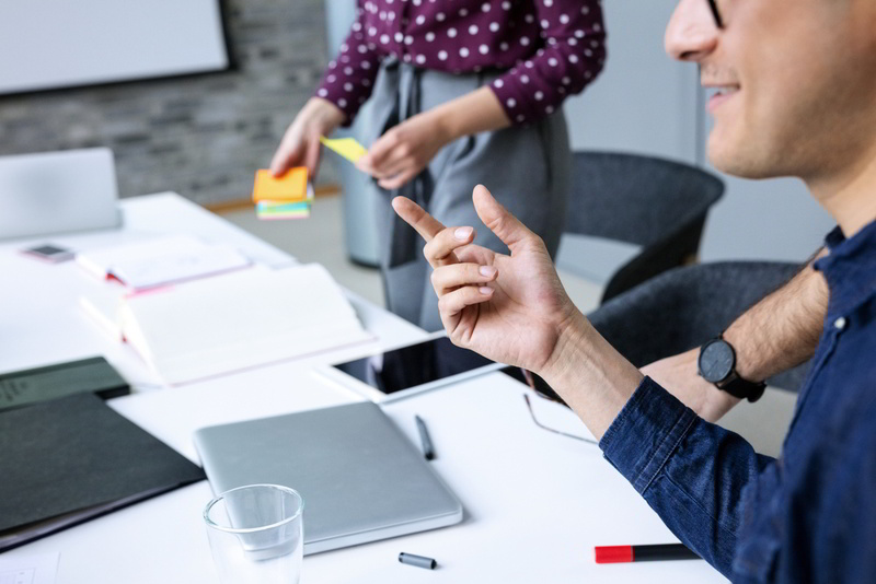 Auschnitt mit Blick auf einen Tisch in einer Workshopsituation: ein Mann gestikuliert, eine Frau sortiert stehend Unterlagen