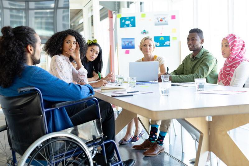Wielfalt: Um einen Tisch herum sitzt eine Gruppe sehr unterschiedlicher Menschen, darunter ein mensch mit Rollstuhl.