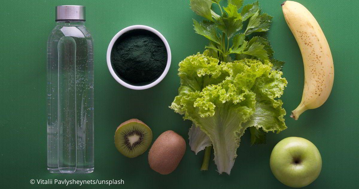 auf einer grünen Unterlagen liegen Zutaten für einen Smoothie: Banane, Apfel, Kiwi und Salatblätter