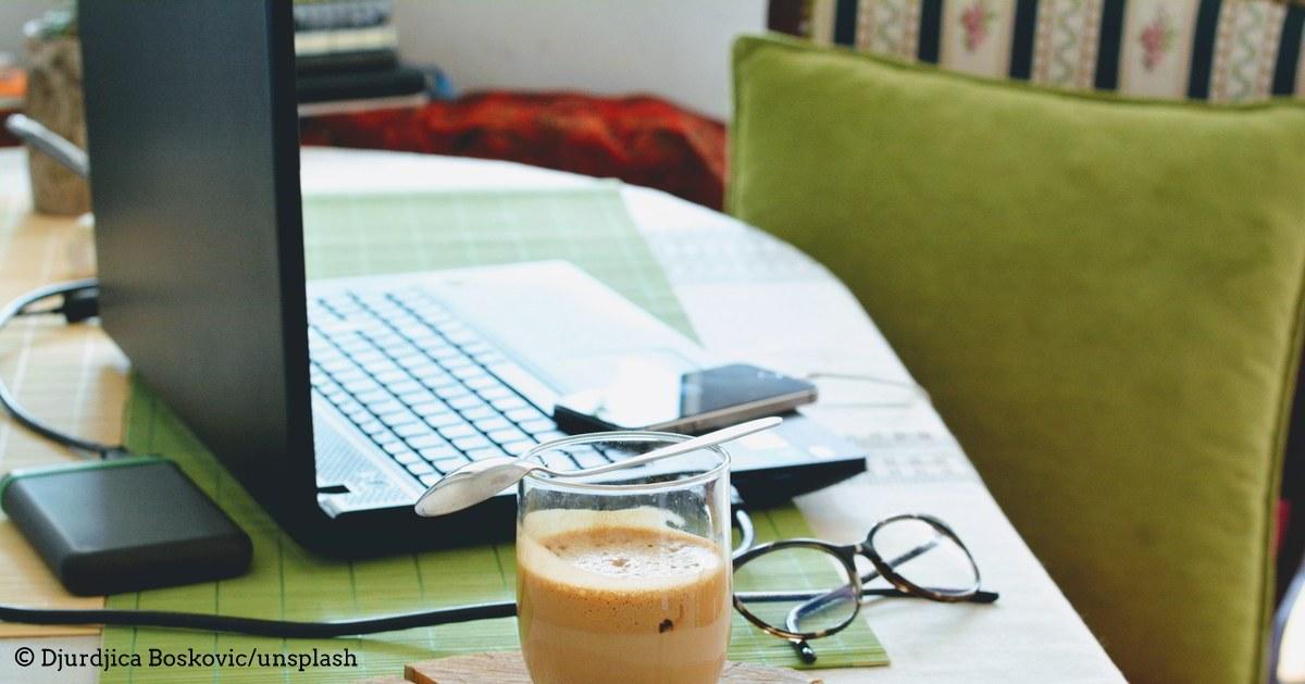 Blick auf einen privaten Schreibtisch mit Laptop, Kissen und Milchkaffee im Glas