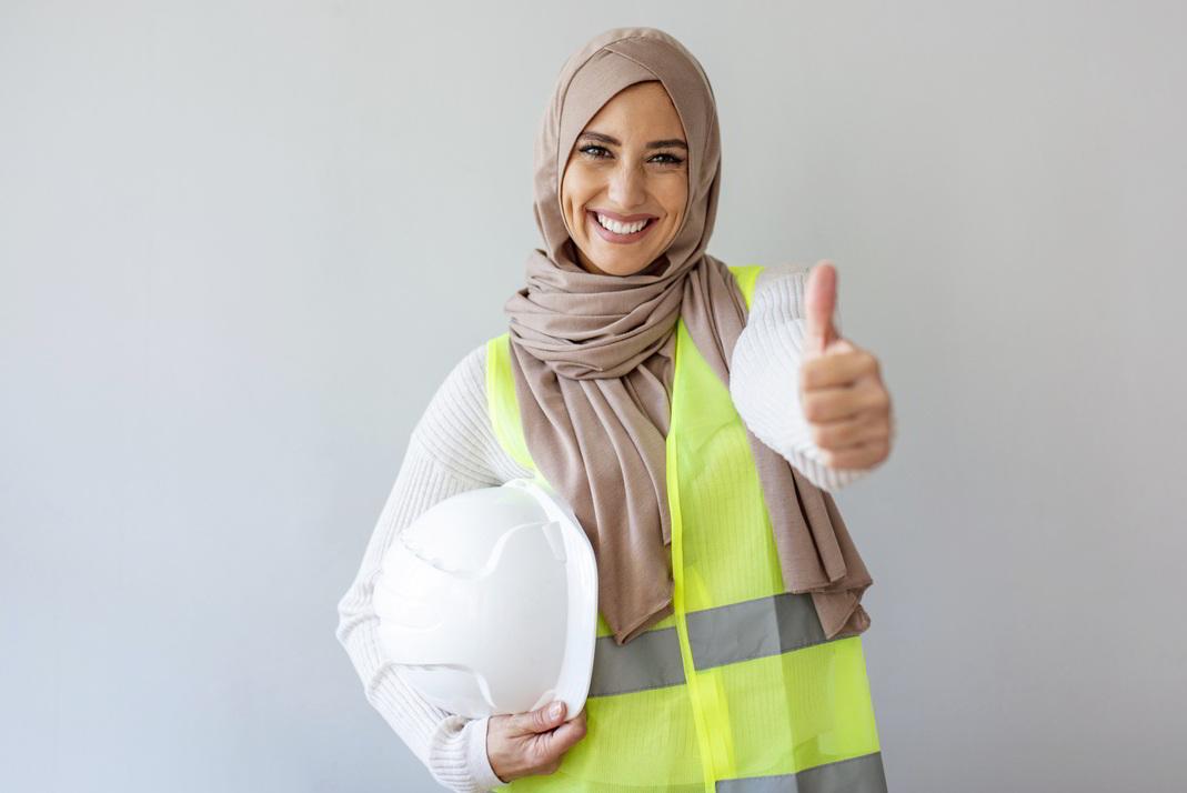 Junge Frau mit Kopftuch und Bauhelm im Arm zeigt Daumen hoch