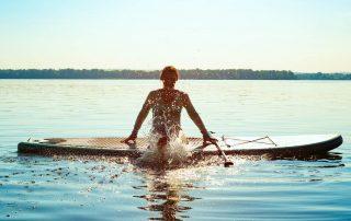 Auf einem See sitzt eine Person quer auf einem Standup-Paddle in sehr hellem Sonnenlicht