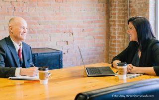Kommunikation am Arbeitsplatz: Ein älterer Mann und eine Frau bei einer Besprechung