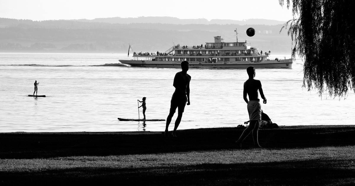 Schwarz-weiß-Bild wie ein Schattenriß: Zwei Männer spielen Volleyball, dahinter auf dem See sind zwei Standup-Paddler und ein Ausflugsschiff zu sehen