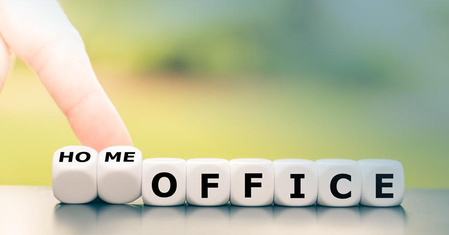 Ein Zeigefinger schiebt zwei von acht Buchstabenwürfeln so dass sich das Wort Homeoffice ergibt