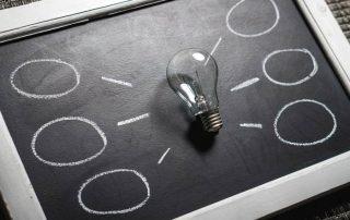 Auf einer kleinen Schreib-Tafel liegt eine durchsichtige Glühbirne, mit Kreisesind sechs Strahlen und Kreise um sie herum aufgemalt.