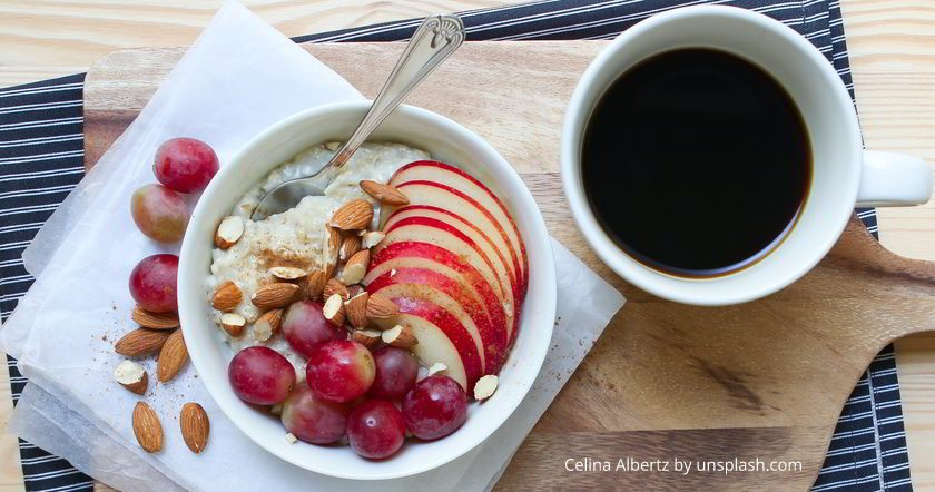 Blick von oben in Müslischale mit frischem Obst, daneben steht eine Tasse mit schwarzem Kaffee