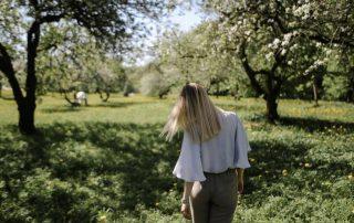Eine Frau läuft über eine Wiese mit blühenden Obstbäumen