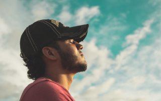 Junger Mann mit kleinem Bart und Basecap steht entspannt mit geschlossenen Augen vor einem blauen Himmel mit zarten Wolken