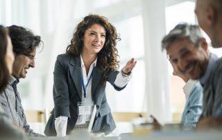 Junge Frau steht am Konferenztisch, fröhliche Stimmung unter den Mitarbeitenden